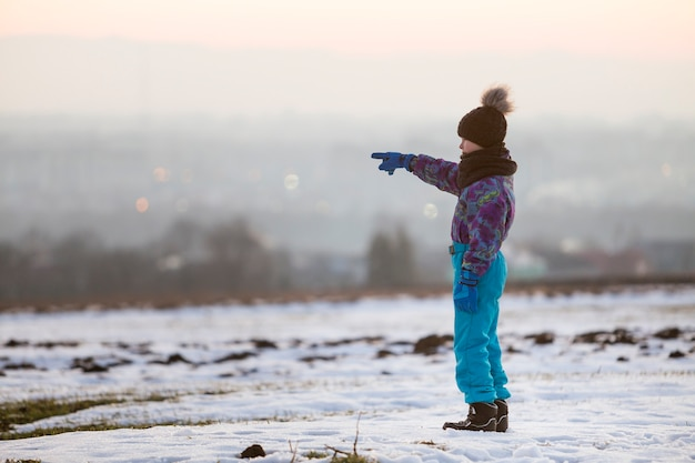 Little boy standing outdoors alone on a snow-covered winter field