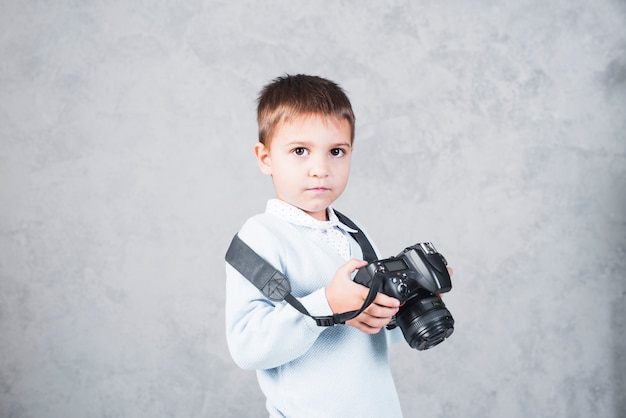 Little boy standing with camera