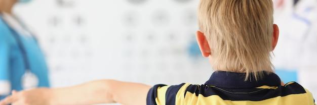 小さな男の子は、医師の手紙を持ってスタンドの前の眼科医のオフィスに立っています