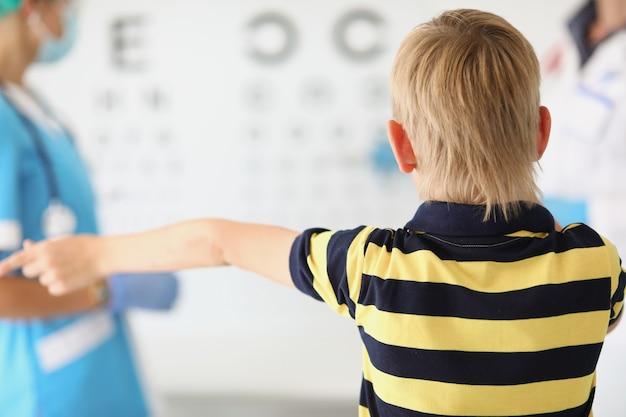 Маленький мальчик стоит в кабинете офтальмолога перед трибунами с письмами врачу