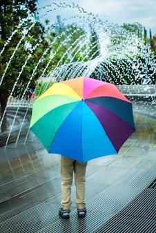 噴水の傘の下に立つ少年