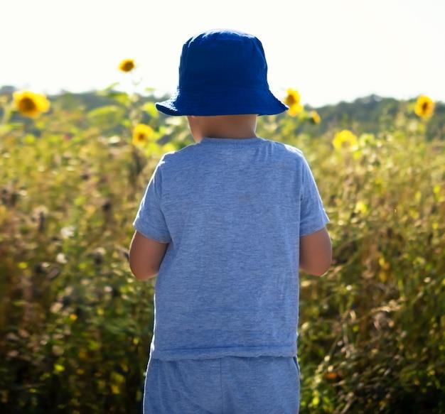 어린 소년은 자연 속에 등을 대고 서 있다