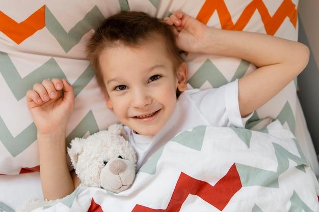 Маленький мальчик, оставаясь в постели со своей любимой игрушкой