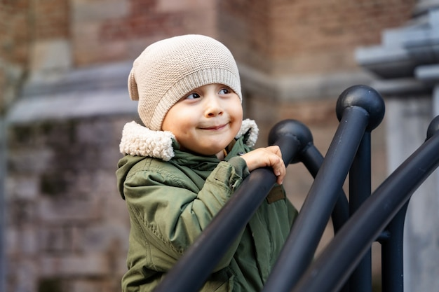 Little boy staying outdoors and  holding onto the railing near the building. child walking in the street. toddler wearing warm parka and a funny hat looking aside, close up.