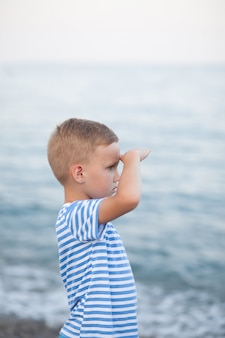Little boy in striped t-shirt playing on the beach with blurry background by the sea
