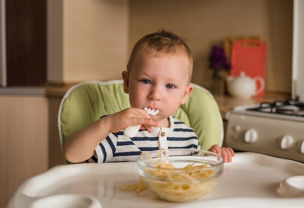 A little boy in a striped t-shirt sits in a high chair and eats pasta. look at the camera.