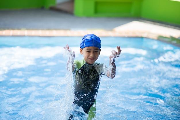 Маленький мальчик учится в классе плавания с учителями