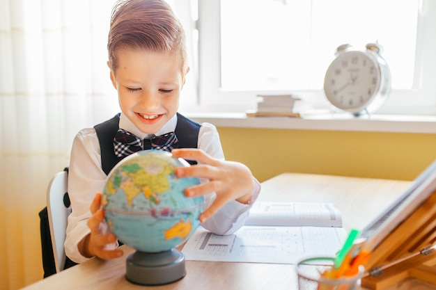 Little boy studying or completing home work on study table with a globe and workbook