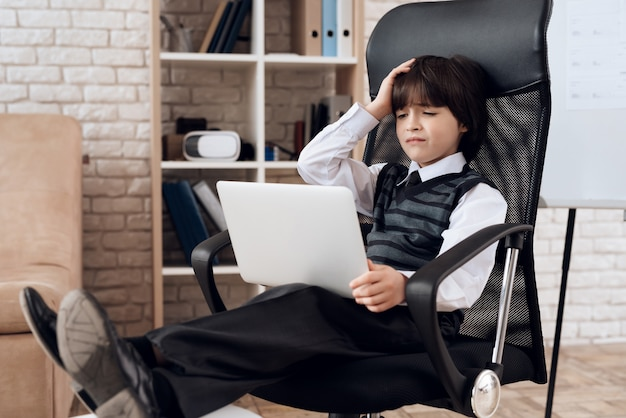 A little boy in a suit presents himself as a businessman.