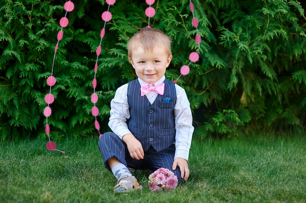Little boy in a suit with a bouquet sitting on the grass