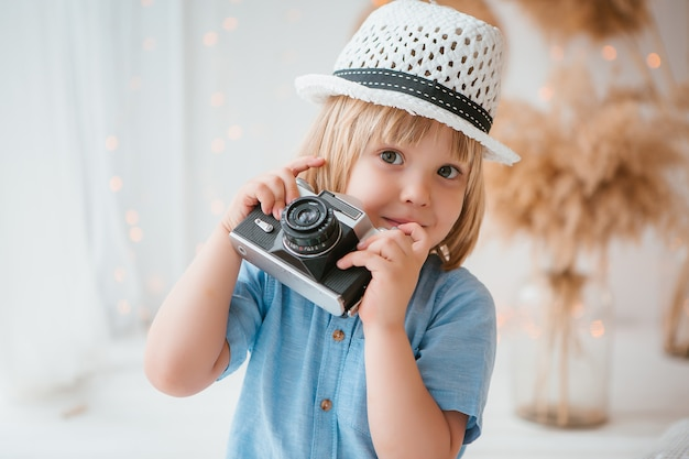 Little boy in a summer hat holding a camera
