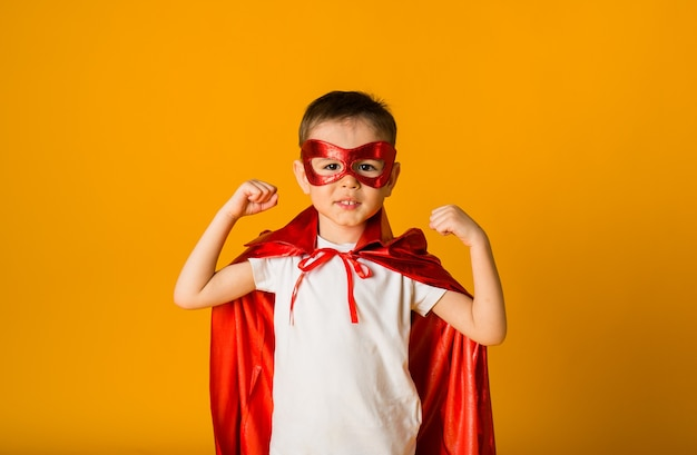 Little boy in a superhero costume shows power on a yellow surface with space for text