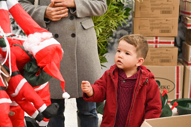 Little boy in surprise looks at santa claus toy in the store