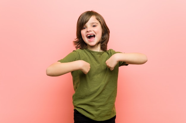 Little boy surprised pointing with finger, smiling broadly.