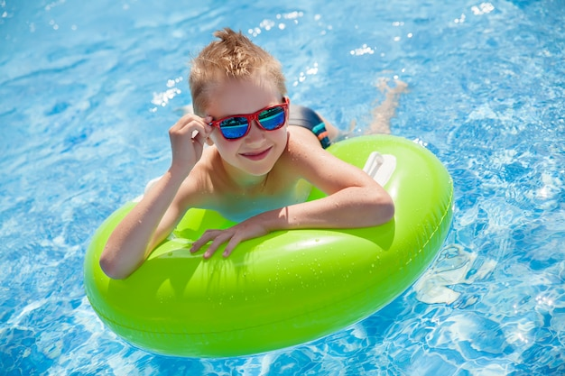 Little boy swimming in the pool with big bright green rubber ring