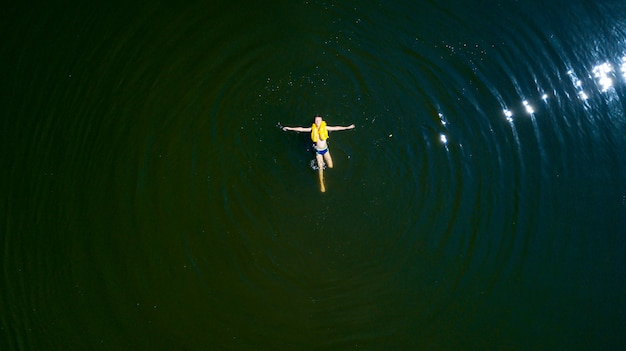 A little boy swims lying on his back in the middle of a river in the summer.