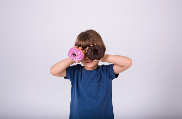 A little boy in a t-shirt closed his eyes two donuts on a white background with a place for text
