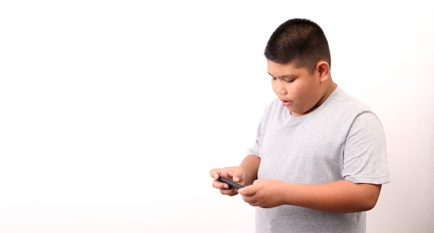 Little boy in t-shirt presenting smart phone on white background in studio.