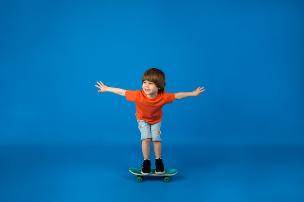 A little boy in a t-shirt and shorts rides a skateboard on a blue surface with space for text