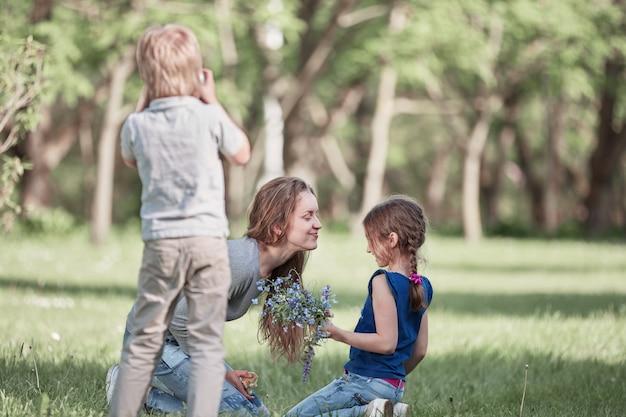 어린 소년은 공원에서 산책하는 그의 어머니와 여동생의 사진을 찍습니다.
