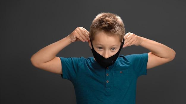 小さな男の子は彼の手で彼の黒いマスクを脱ぎます。白人の子供は安堵と笑顔で呼吸します