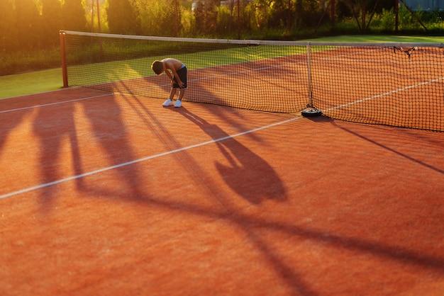 ハードテニスのトレーニングの後、リラックスするのに数分かかる男の子。夏の暑い日に外にテニスフィールドに立っています。
