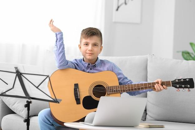 自宅でオンラインで音楽のレッスンを受けている小さな男の子
