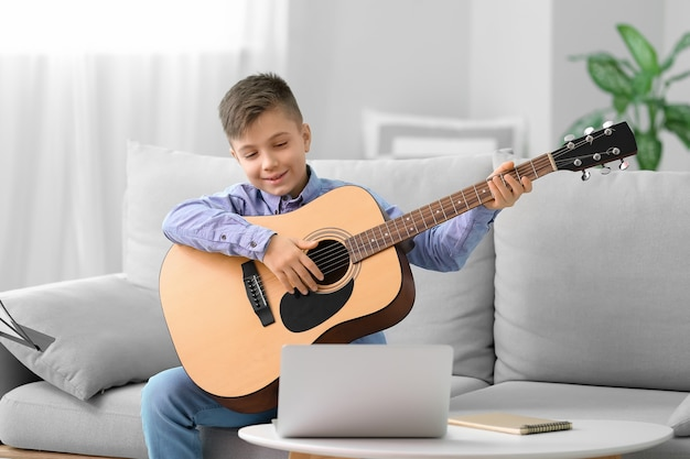 Little boy taking music lessons online at home
