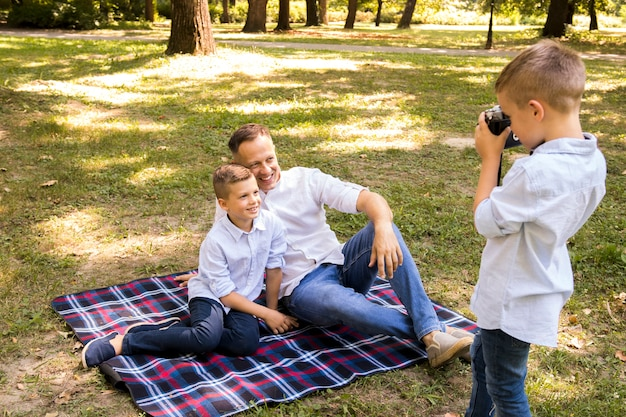 Little boy taking a photo of his brother and father