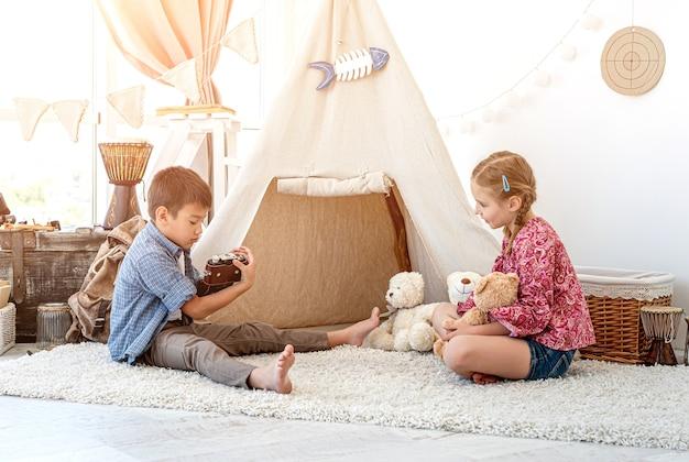 Маленький мальчик фотографирует маленькую девочку с ретро-камерой в детской комнате