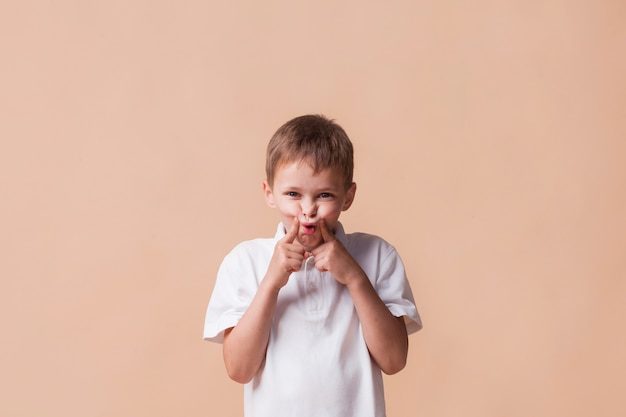 Little boy teasing and looking at camera standing near beige background