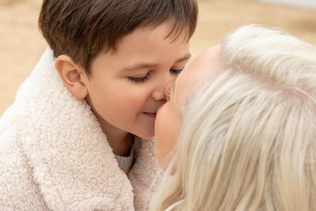 Маленький мальчик нежно целует свою маму на песке осенью в теплой одежде