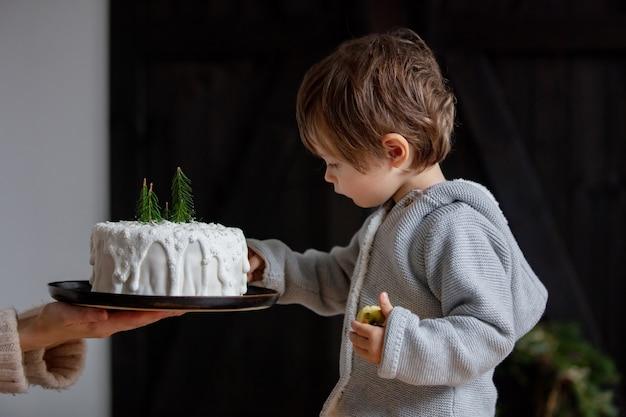 집에서 생일 케이크를 테스트하는 어린 소년