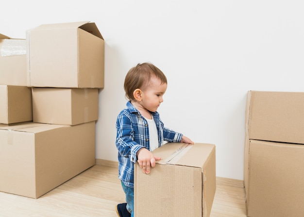 Little boy toddler holding cardboard box in his new house