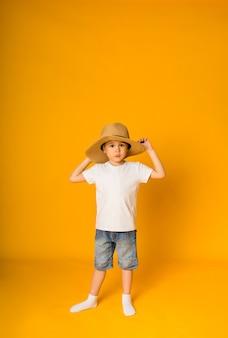 麦わら帽子をかぶった小さな男の子の幼児が立って、テキスト用のスペースがある黄色い表面でカメラを見ます
