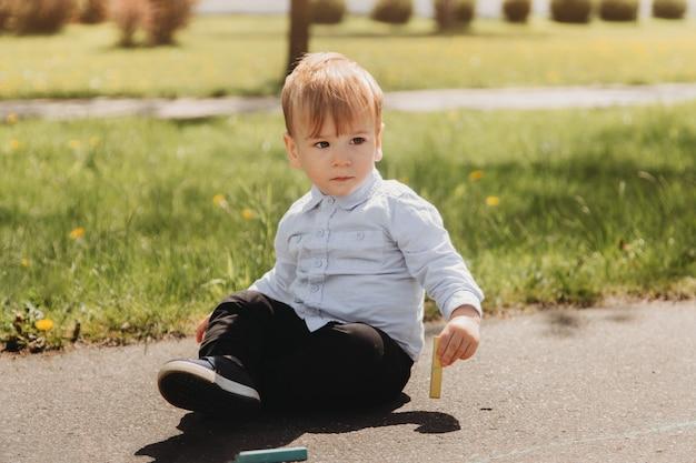 어린 소년 todler는 공원에서 여름에 아스팔트에 분필을 그립니다.