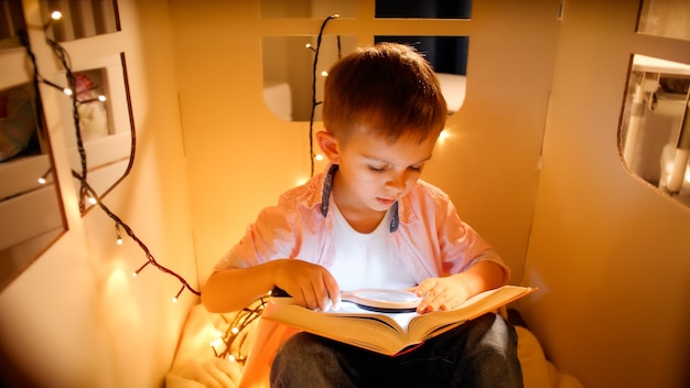 Little boy in toy house with light garlands reading book at night. concept of child education and reading in dark room.