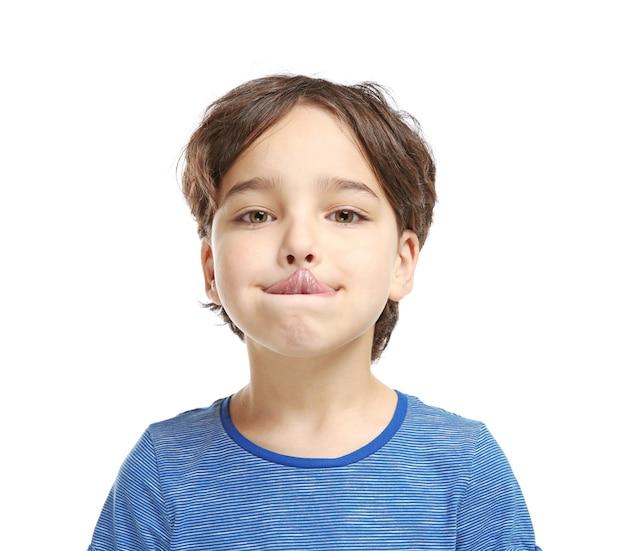 Тренировка маленького мальчика произносит буквы на белой поверхности