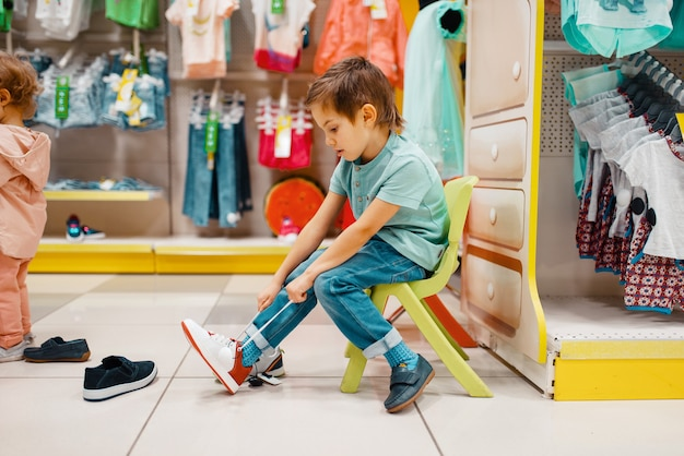 아이 스토어, 측면보기에서 신발에 노력하는 어린 소년. 슈퍼마켓, 가족 쇼핑, 젊은 고객에서 운동화를 선택하는 아들
