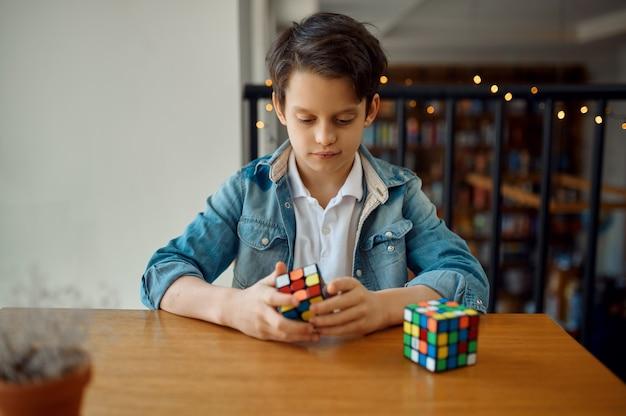Маленький мальчик пытается решить куб головоломки. игрушка для тренировки мозга и логического мышления, творческой игры, решения сложных задач.