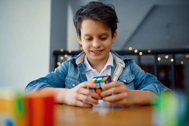 Маленький мальчик пытается решить кубики головоломки. игрушка для тренировки мозга и логического мышления, творческой игры, решения сложных задач.