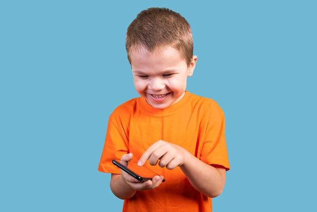 小さな男の子は、青い背景で隔離のスマートフォンと笑顔を使用しています。あらゆる目的のために。