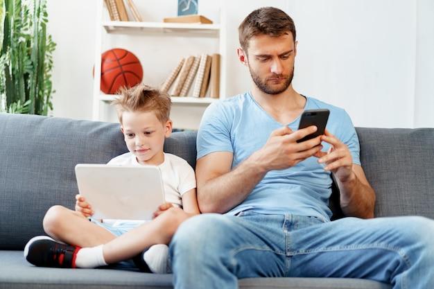 디지털 태블릿을 사용하는 어린 소년과 스마트 폰을 사용하는 그의 아버지는 집에서 소파에 함께 앉아
