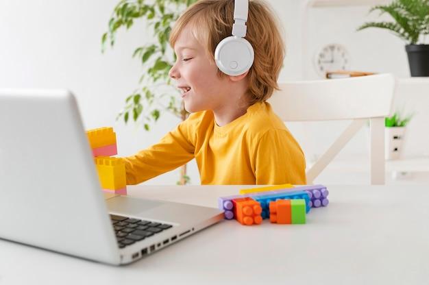 집에서 헤드폰과 노트북을 사용하는 어린 소년