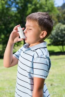 Little boy using his inhaler