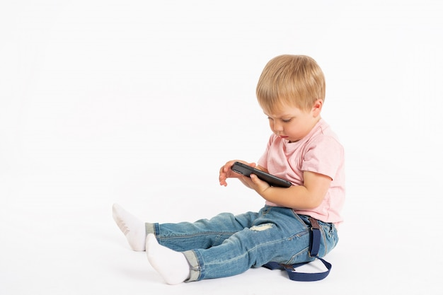 Little boy using mobile phone. child playing on smartphone. technology, mobile apps, children and parental advisory, lifestyle