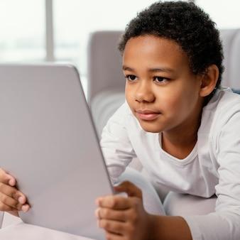 Маленький мальчик с помощью планшета