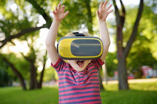 Little boy using virtual reality headset outdoor. vr, vr glasses, augmented reality experience.
