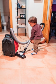 Little boy vacuuming at home doing his homework