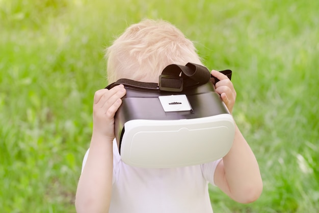 Little boy in a virtual reality helmet on a  of green grass